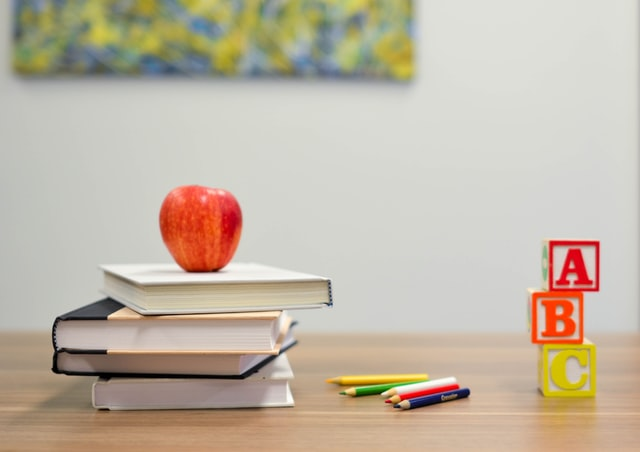 books, colored pencils, blocks, and an apple on a desk