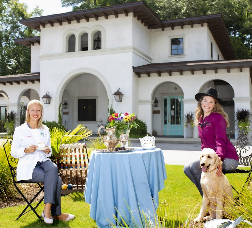 two women and dog sitting at a table outside of large home