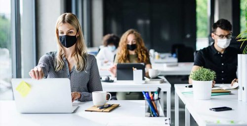 people working at desks with masks on during pandemic